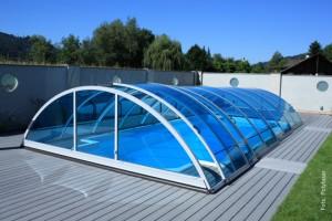 """Wie die meisten halbrunden, halbhohen Schwimmbadüberdachungen ist auch das Modell """"Rubin"""" von Polyfaser mit Elementen aus SAN-Glas versehen. Polyfaser bietet die UV-beständige Überdachung in verschiedenen Farben an, das Bild zeigt eine blaue Ausführung. Das Dach kann auf einer flachen Laufschiene zusammengeschoben werden."""
