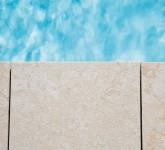 Pool-mit-Heimvorteil-Eine-stilsichere-Poolumrandung-aus-Naturstein-rahmt-das-Becken-ein