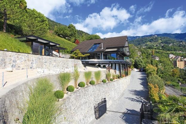 Ready-steady-home_Das-Fertighaus-liegt-an-einem-Hang-gelegen-der-Poolbereich-ist-so-vor-neugierigen-Blicken-geschützt