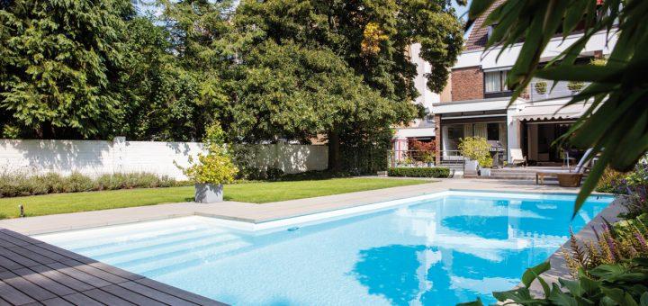 Im-Garten-Eden_Dezent-fügt-sich-der-mit-Holz-umkleidete-Pool-in-die-Gartenumgebung-ein,-seine-geometrischen-Formen-schaffen-Ruhe-und-Balance
